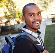 Photo of a smiling young man with a backpack to illustrate that in Christianity there is not the burden to earn God's acceptance.