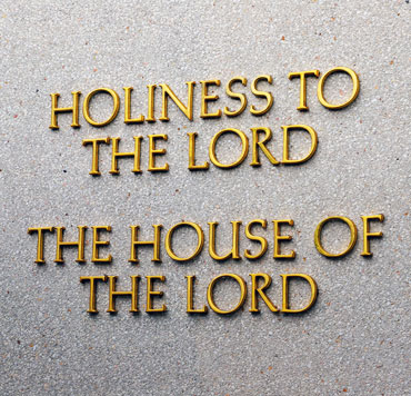 """Photo of a plaque outside a Mormon church building that reads """"Holiness to the Lord / The house of the Lord"""""""