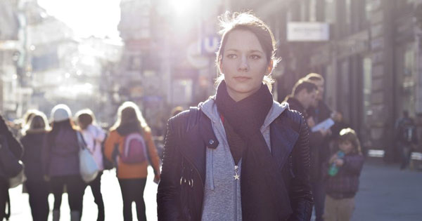 Does God Exist? - Photo of young woman walking in a crowded city street, looking deep in thought.