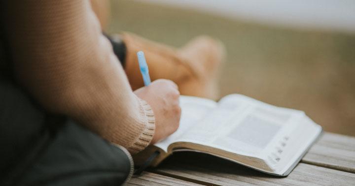 мъж, който пише бележки в книга