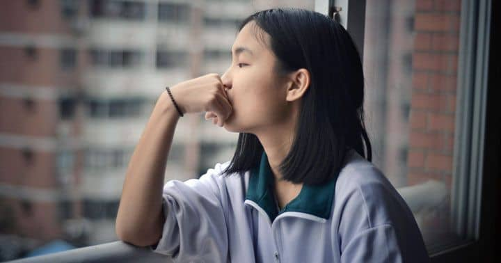 The beginning of time and origin of the universe - Photo of young woman with a thoughtful expression, looking out of a window.