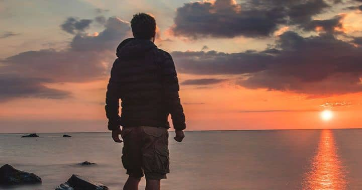 мъж, наблюдаващ морето